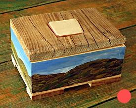 Caja con cerámica, montañas y cielo